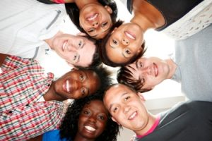 group of multiracial young students huddled together